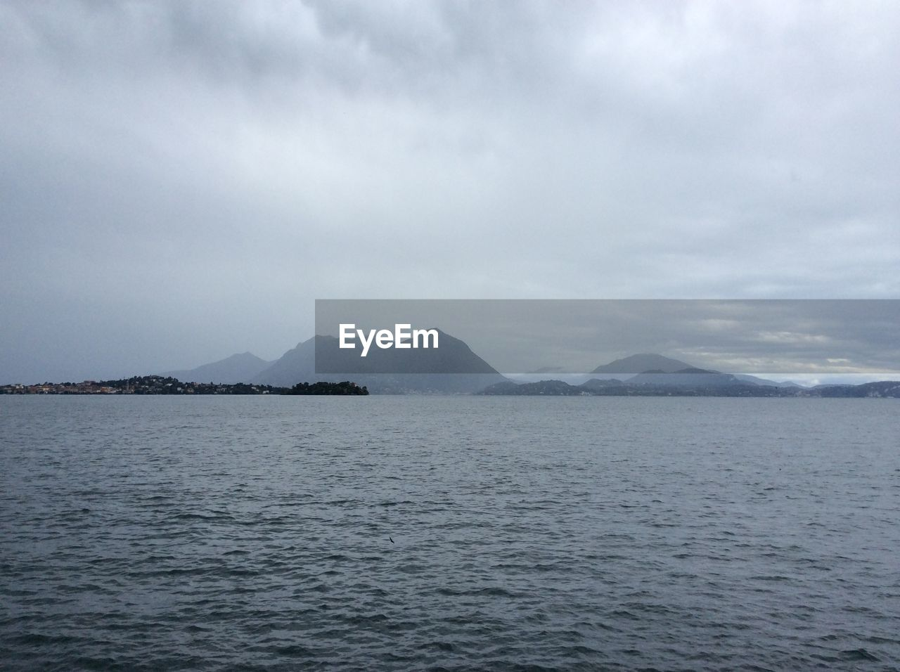 Scenic view of lake maggiore against cloudy sky