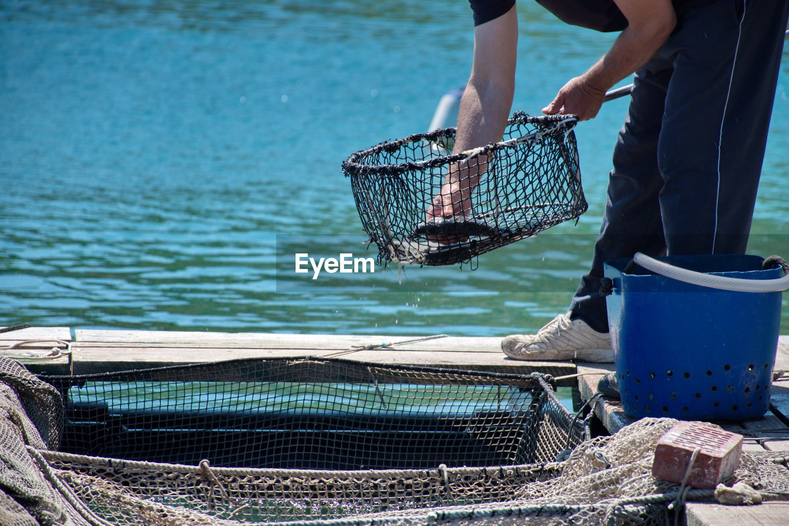Midsection of man working in fish farm and catching fish
