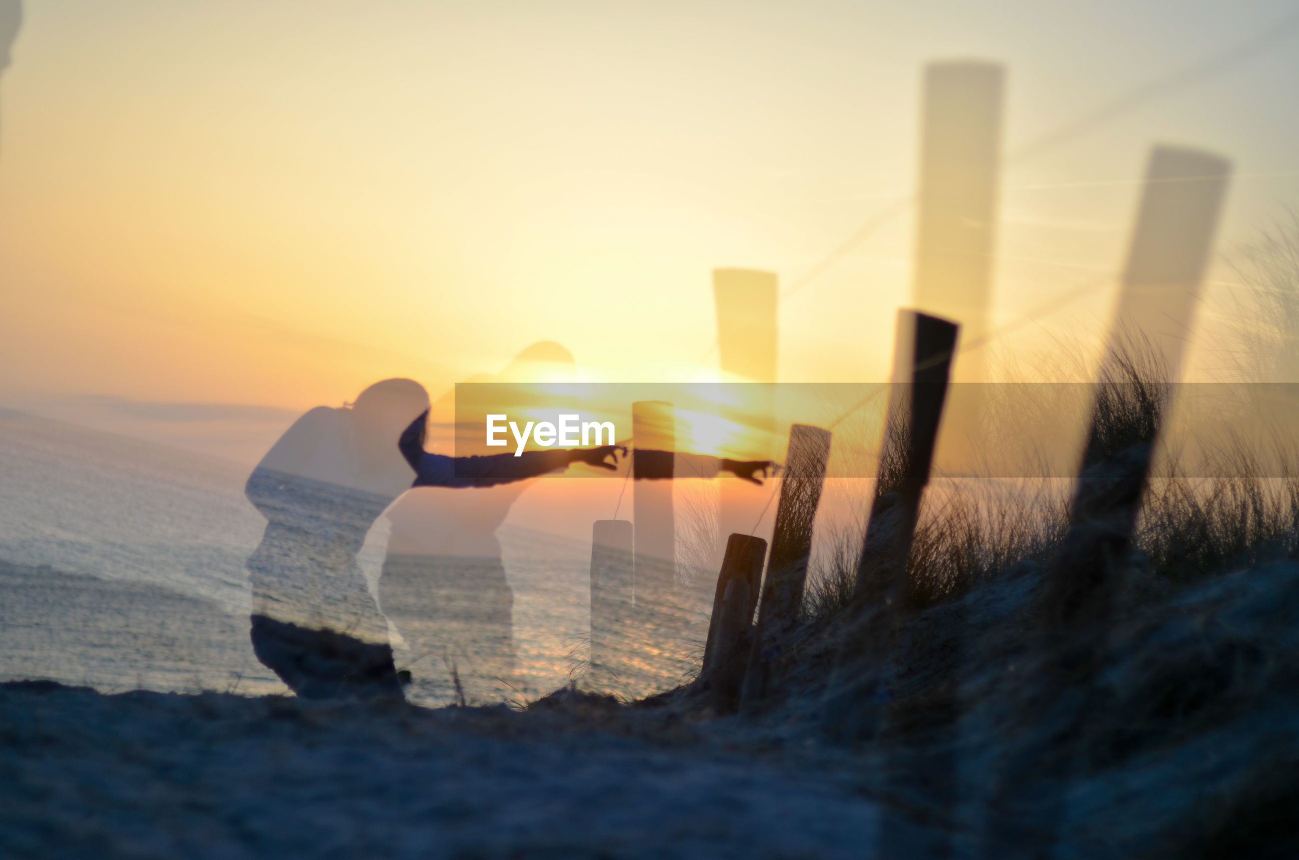 Digital composite image of woman at beach against sky during sunset