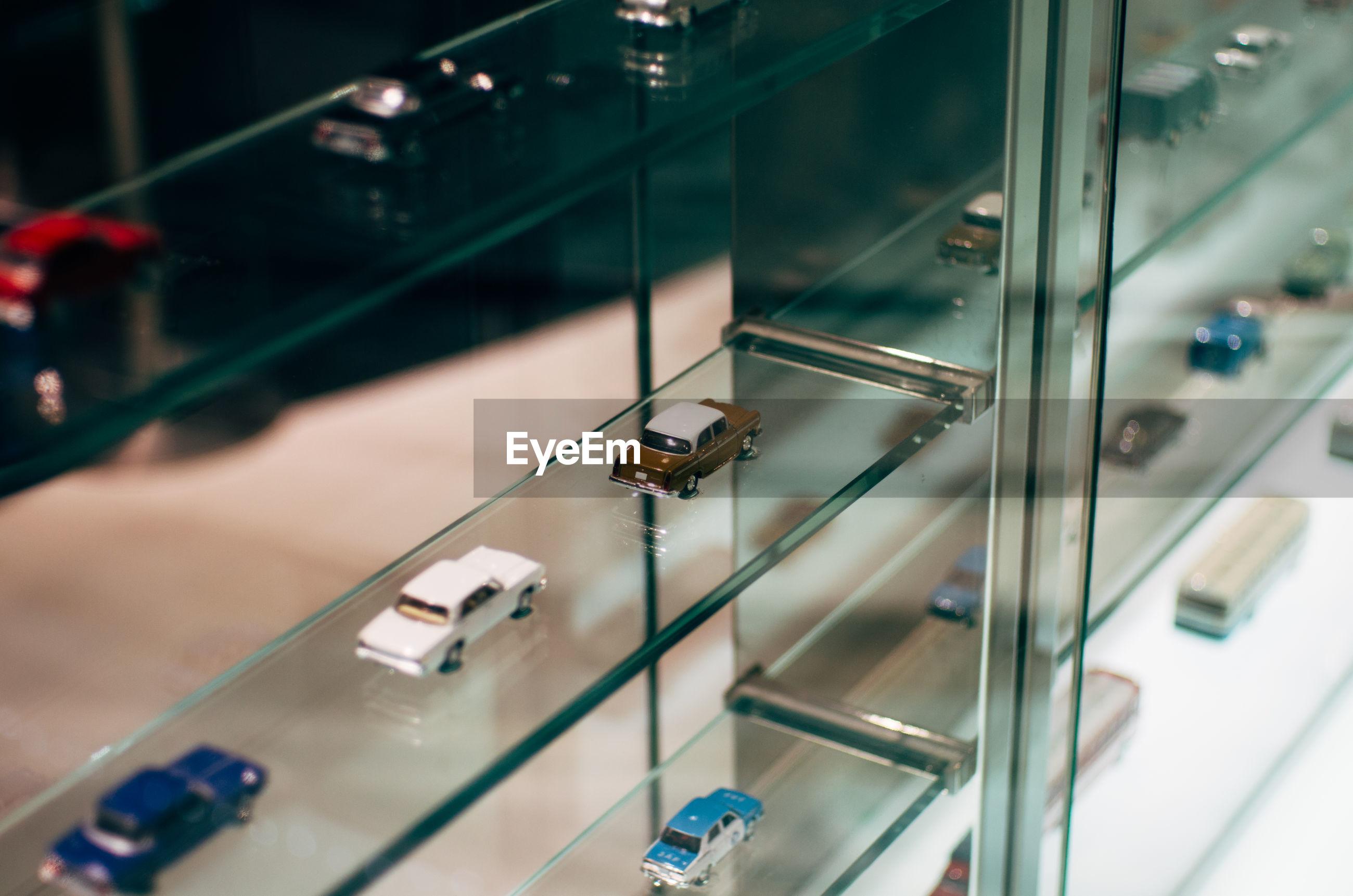 Miniature cars on glass shelf