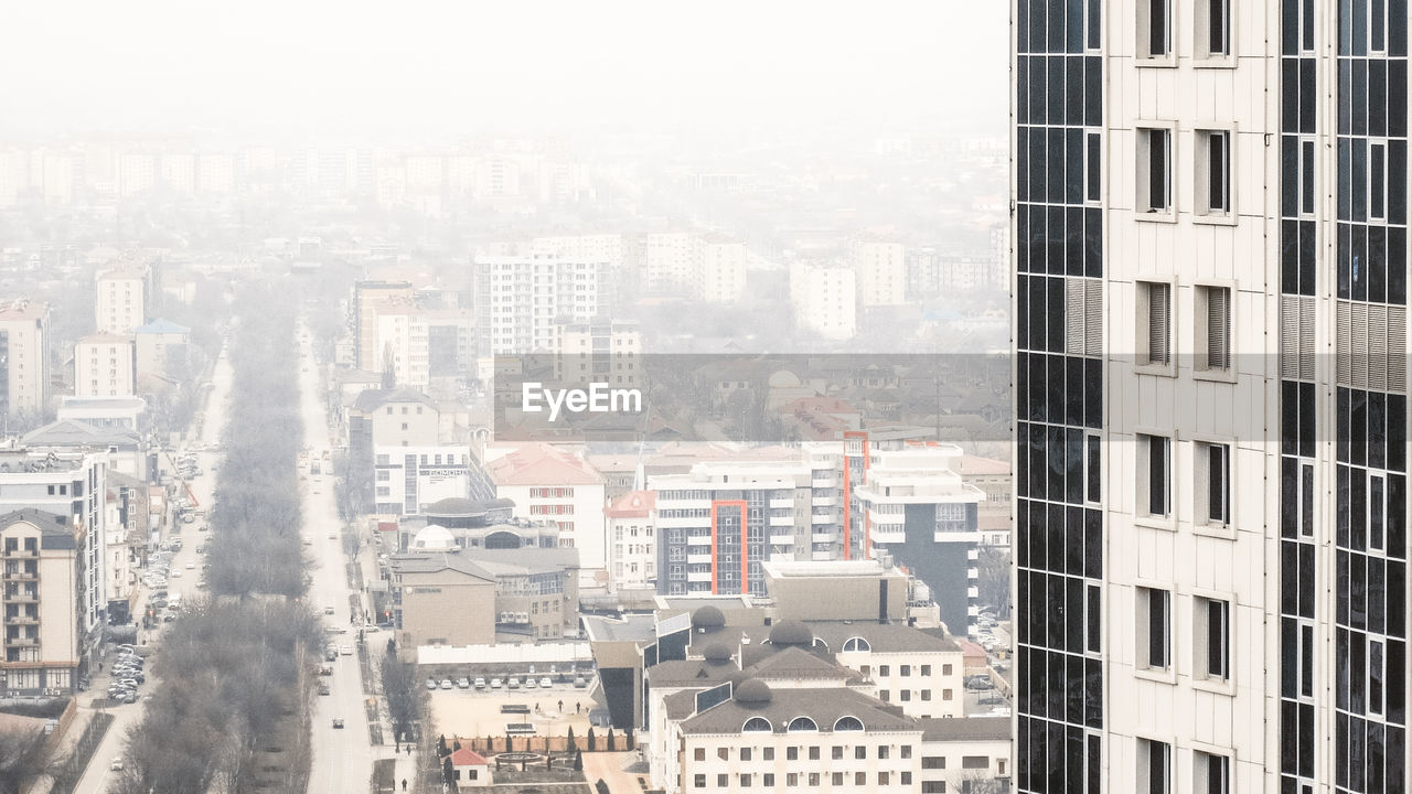 building exterior, city, architecture, built structure, building, cityscape, residential district, office building exterior, day, no people, nature, outdoors, skyscraper, window, high angle view, modern, fog, city life, tall - high, apartment
