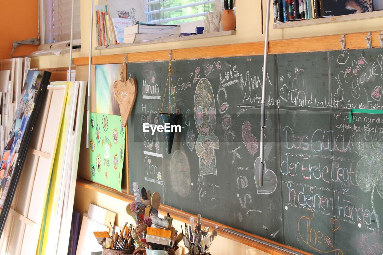 indoors, real people, men, one person, shelf, day, working, blackboard, bookshelf, people