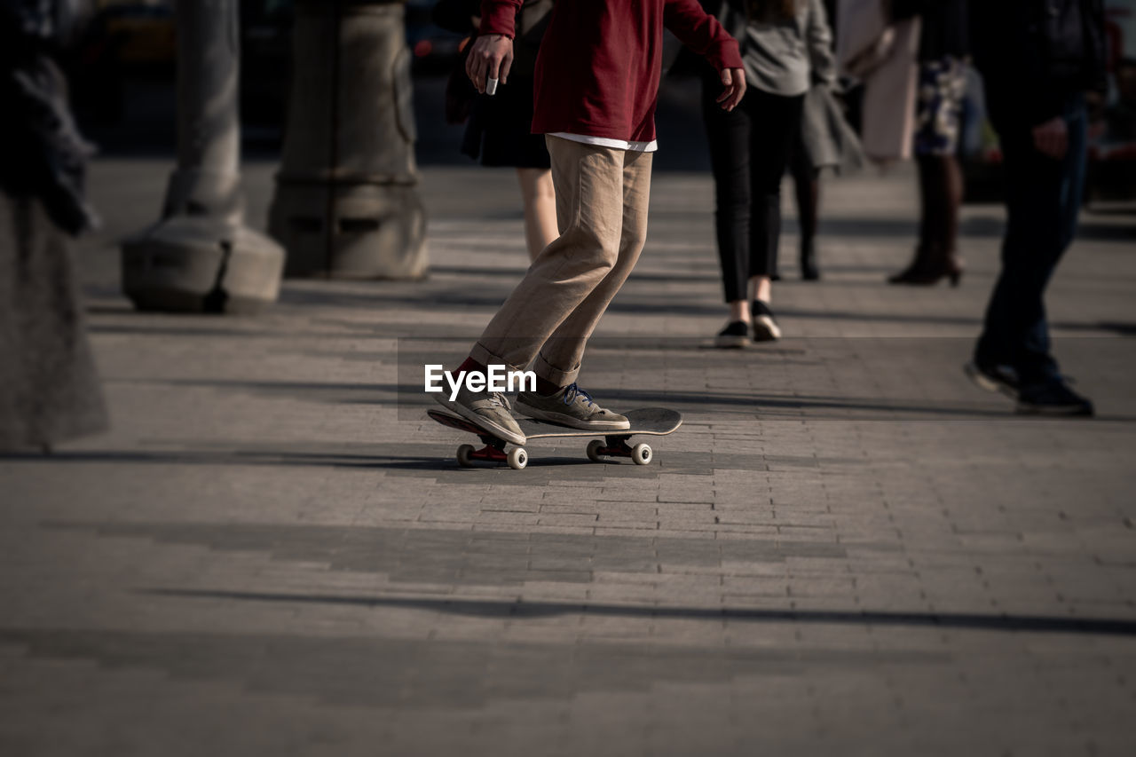 Low Section Of Man Skateboarding On Footpath In City
