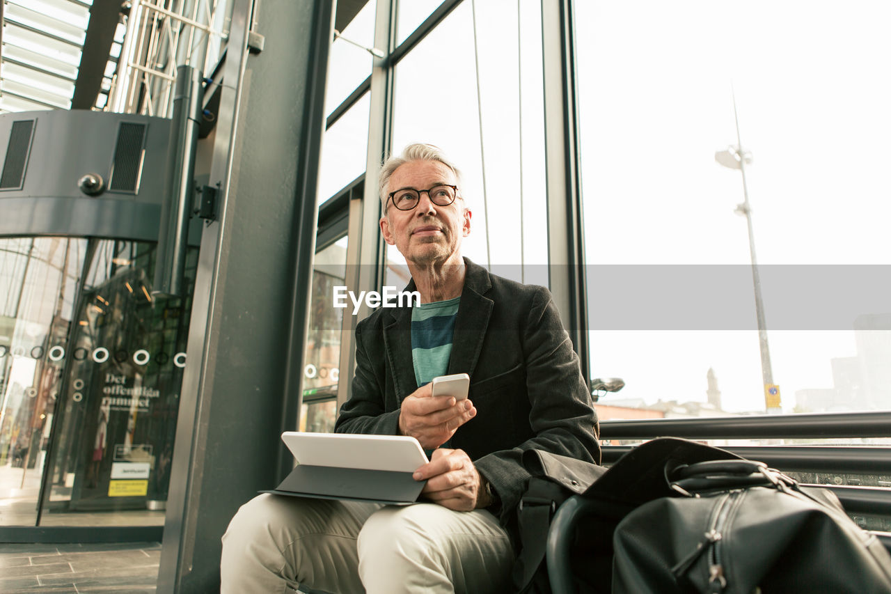 sitting, males, one person, technology, men, adult, front view, three quarter length, connection, wireless technology, real people, glasses, eyeglasses, business person, communication, business, office, computer, mature adult, mature men