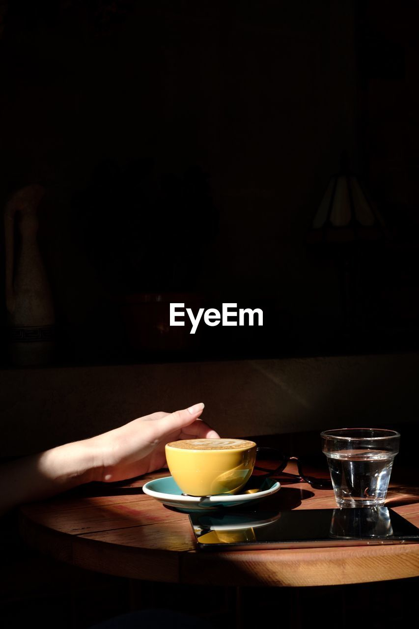 table, food and drink, drink, indoors, human hand, one person, freshness, hand, food, refreshment, plate, bowl, glass, cup, household equipment, drinking glass, real people, human body part, unrecognizable person, crockery, black background, dark, tea cup, breakfast