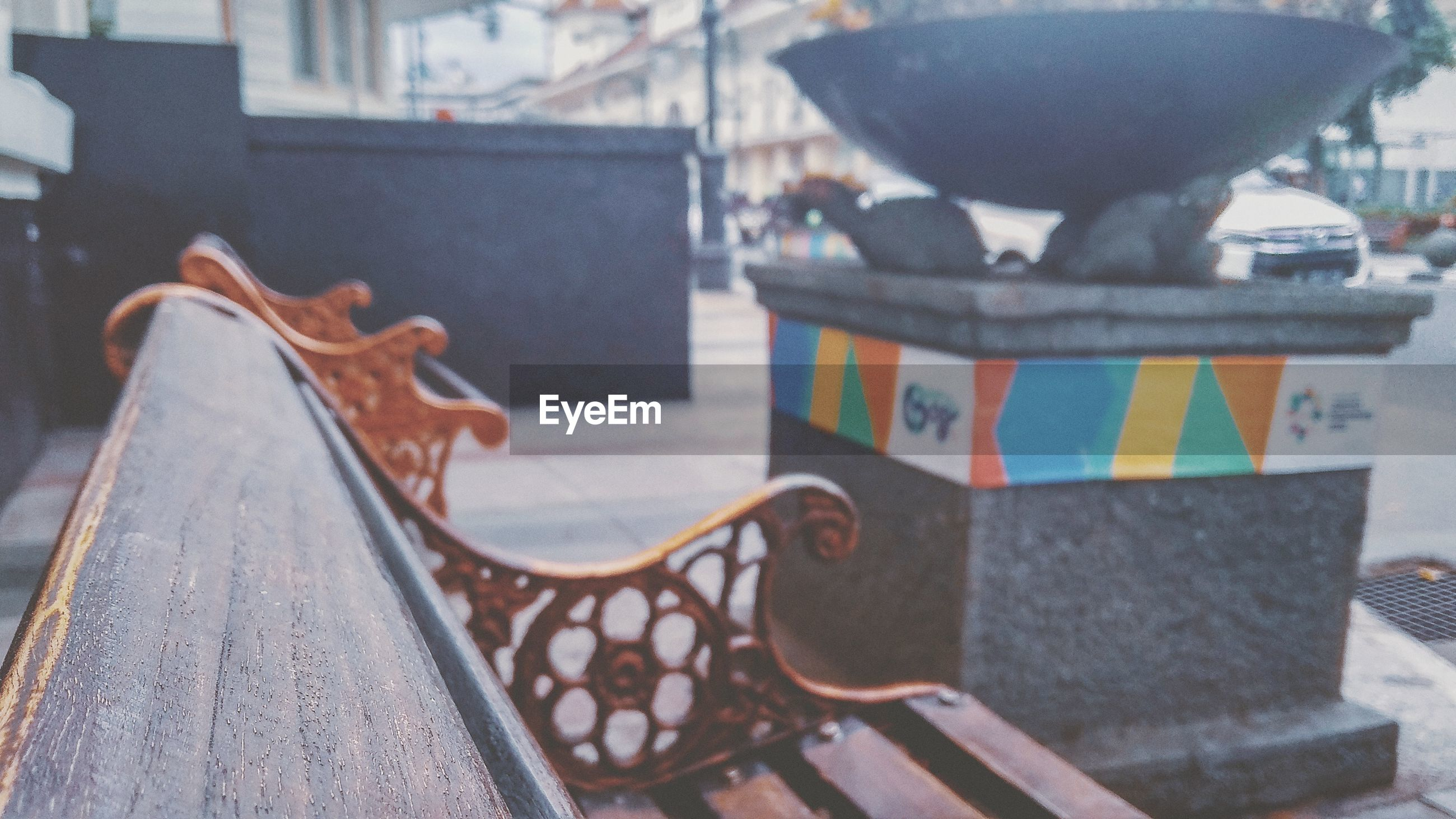 CLOSE-UP OF EMPTY BENCH ON TABLE AGAINST CITY