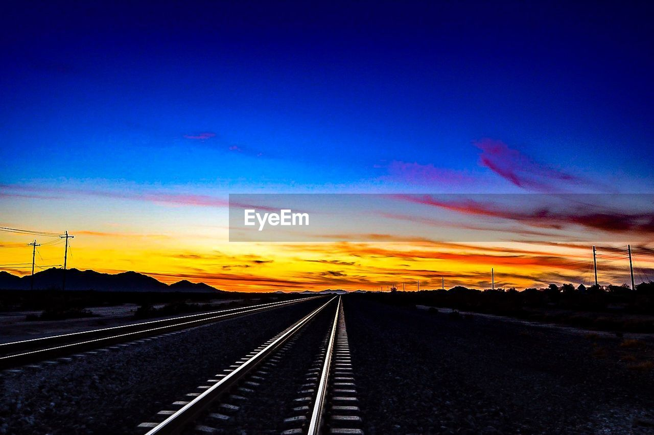 transportation, the way forward, railroad track, rail transportation, no people, sky, road, tranquil scene, nature, cloud - sky, beauty in nature, blue, railway track, sunset, outdoors, scenics, tranquility, landscape, day