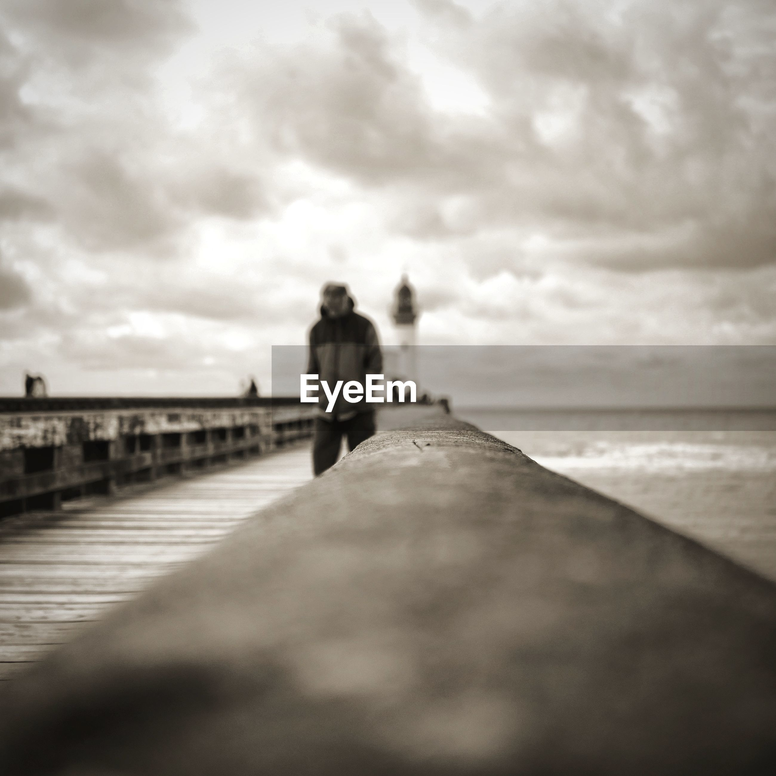 Man walking on pier by railing by sea against cloudy sky