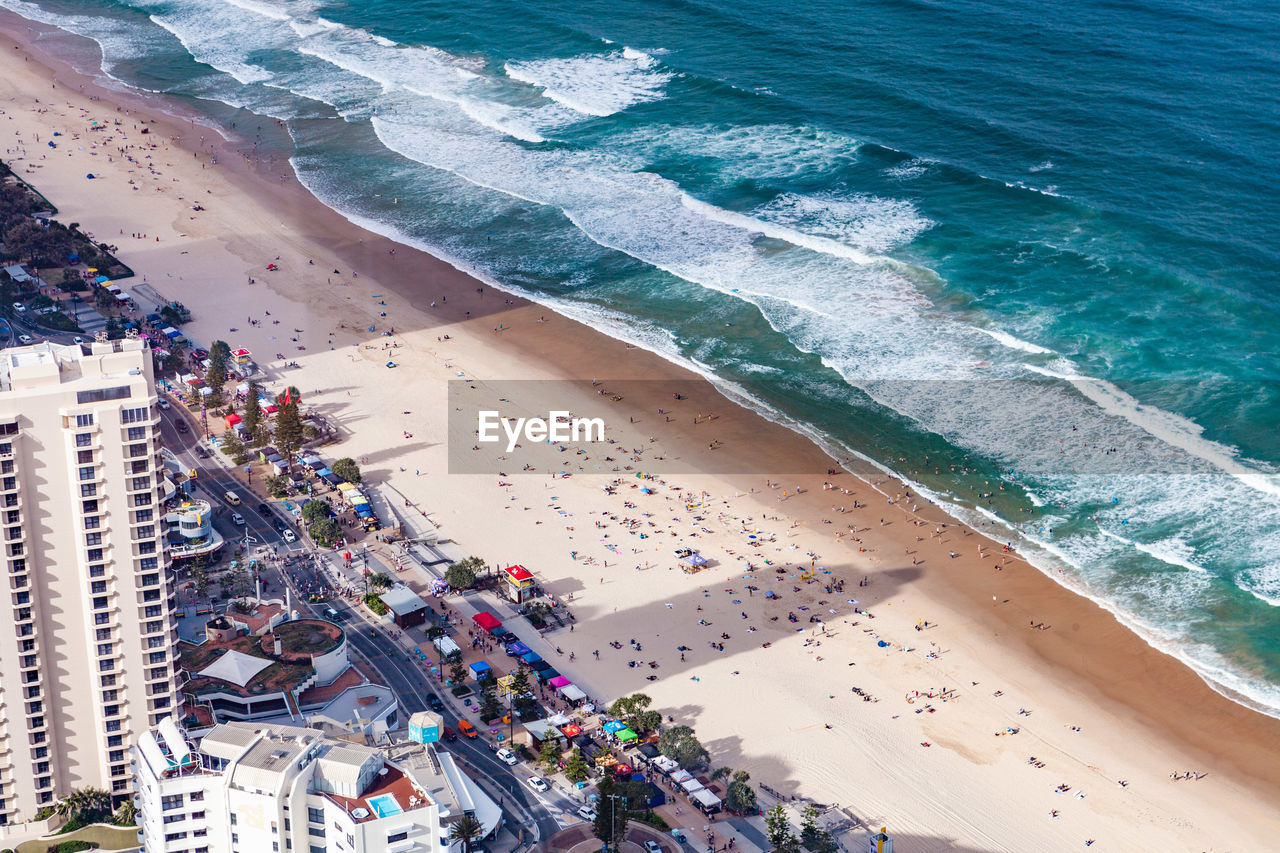 high angle view, sea, water, beach, land, crowd, nature, large group of people, wave, group of people, travel destinations, trip, architecture, vacations, holiday, real people, day, city, outdoors