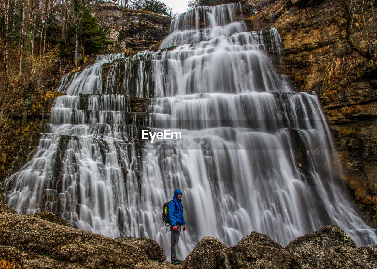 waterfall, motion, scenics - nature, long exposure, beauty in nature, forest, rear view, one person, blurred motion, water, tree, rock, standing, nature, rock - object, flowing water, solid, plant, outdoors, flowing, looking at view, power in nature