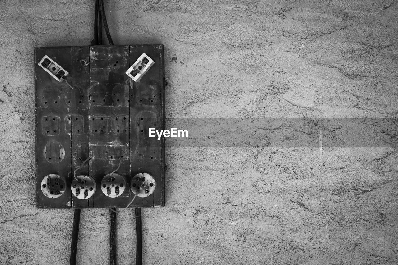text, no people, western script, wall - building feature, connection, day, communication, electricity, close-up, technology, old, control, power supply, indoors, fuel and power generation, push button, wall, mounted, cable, concrete