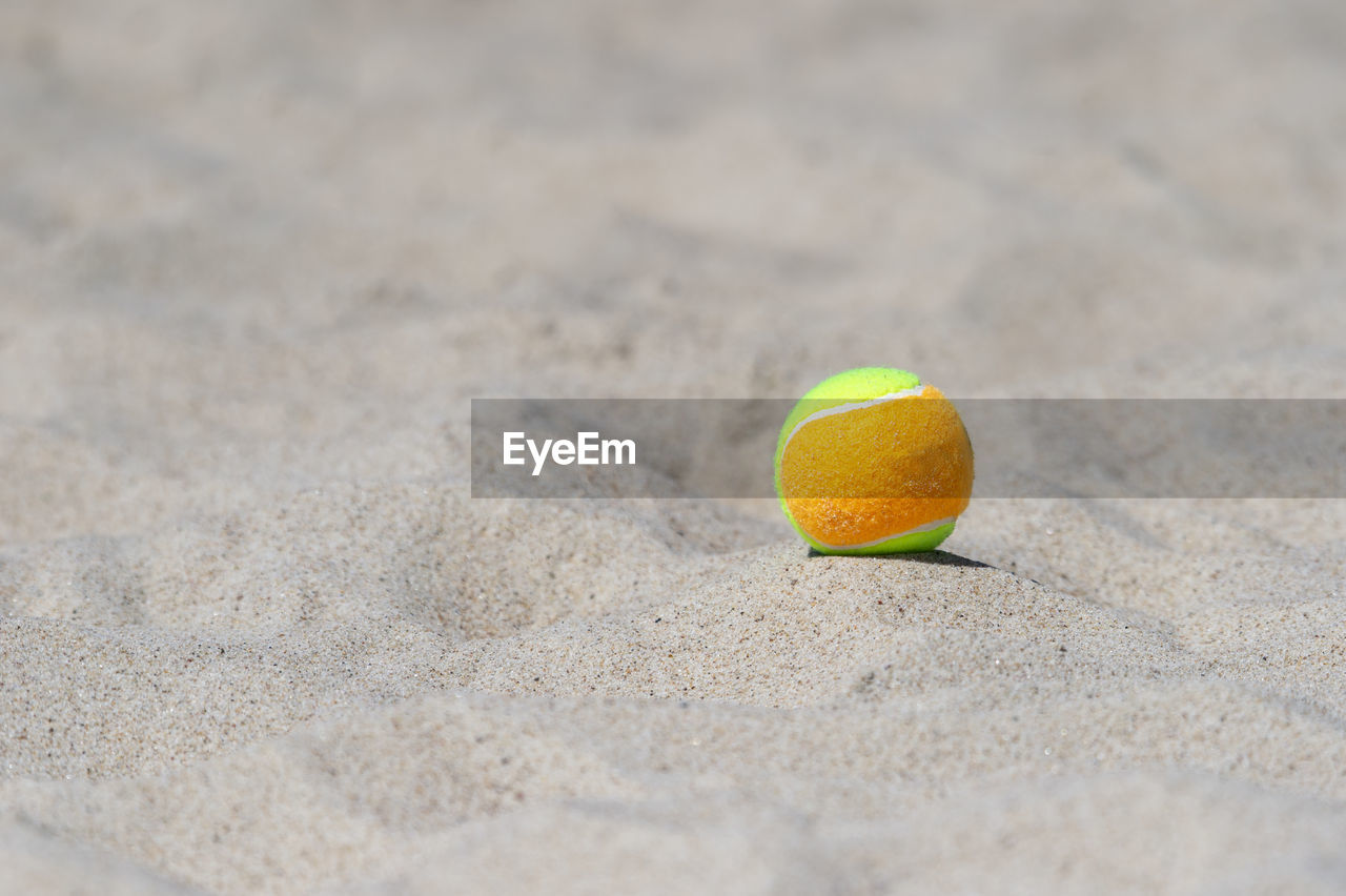 CLOSE-UP OF YELLOW BALL ON BEACH