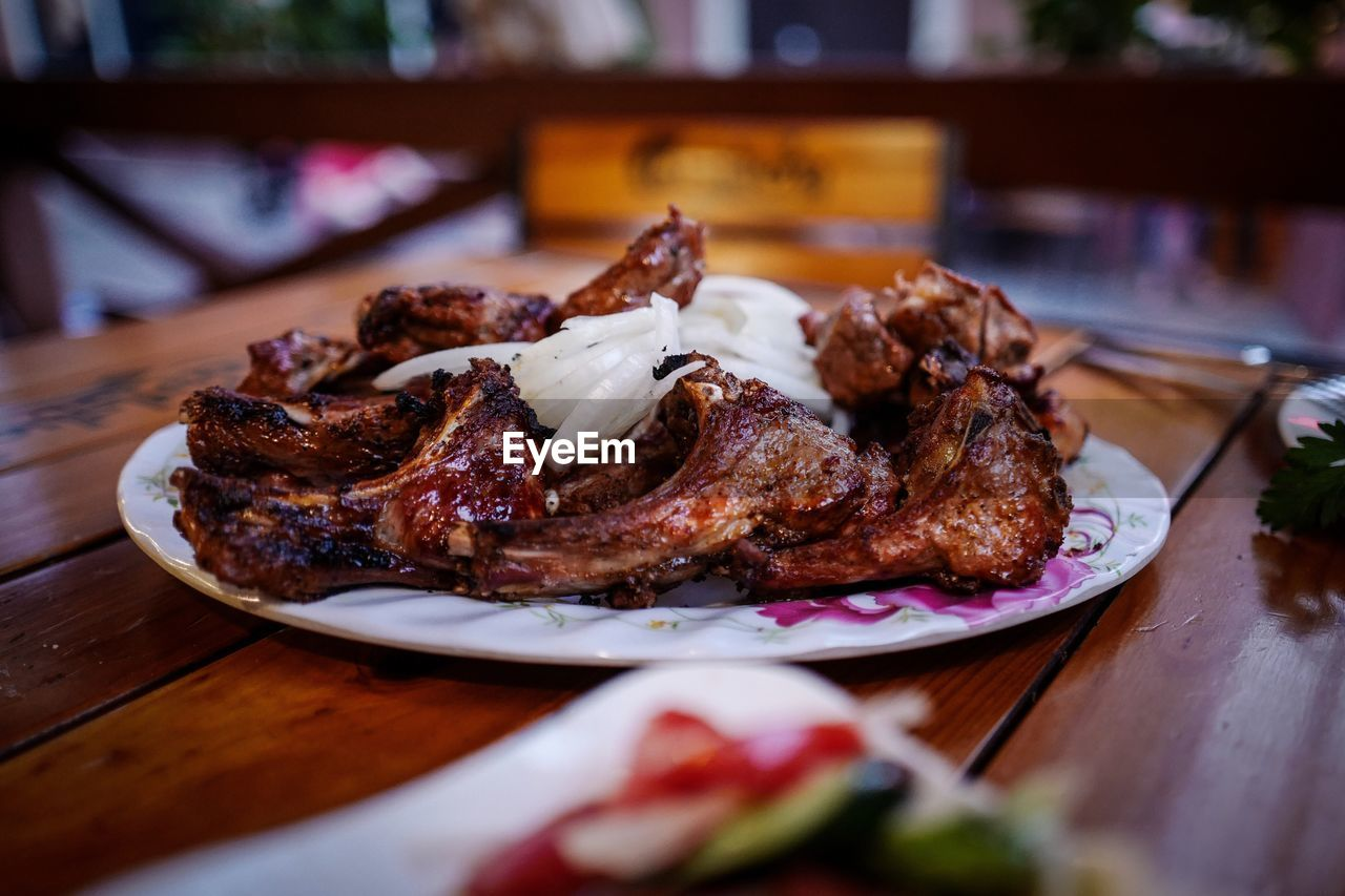 Grilled meat in served plate on table