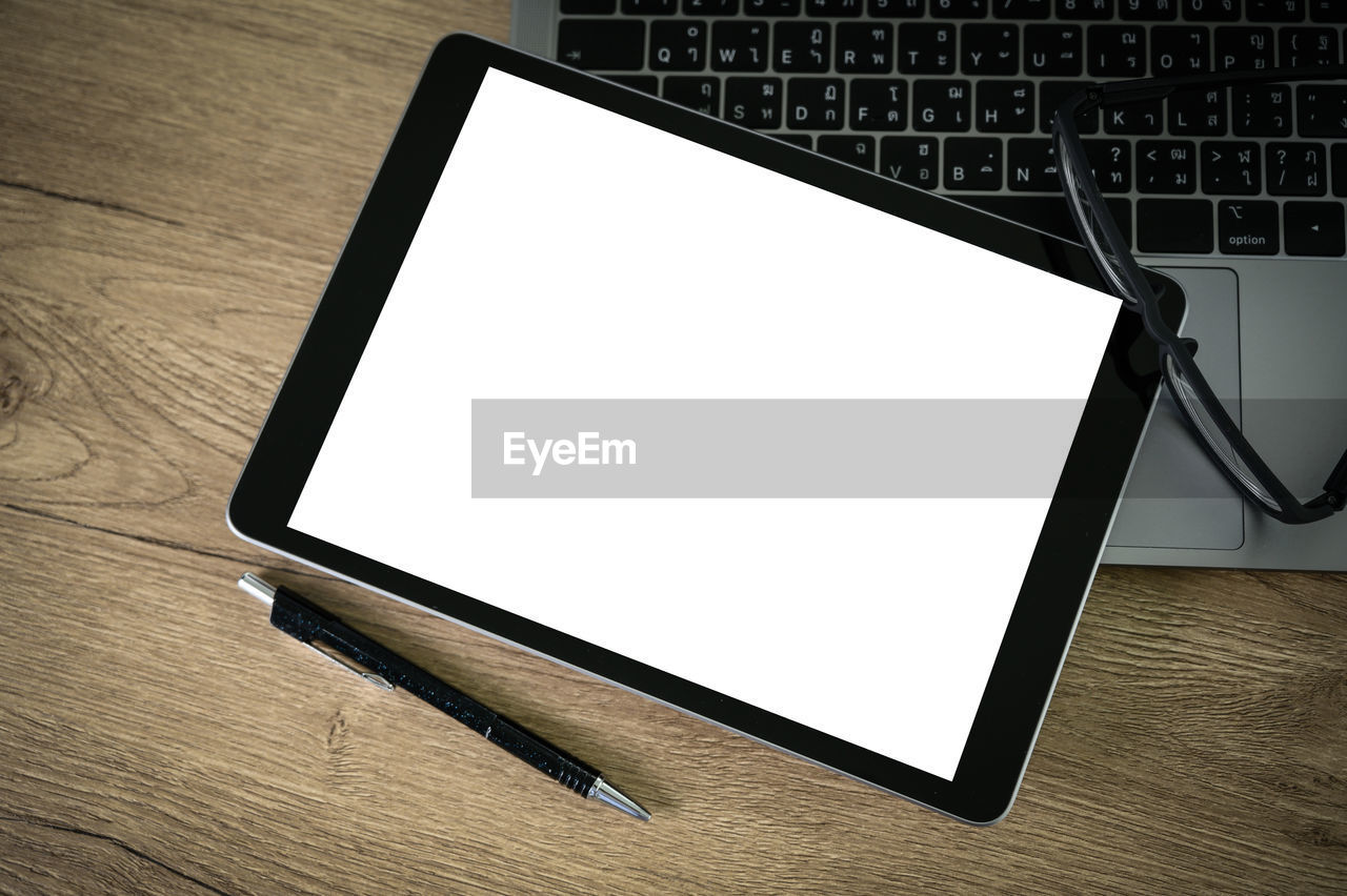 High angle view of blank digital tablet by laptop and pen on table
