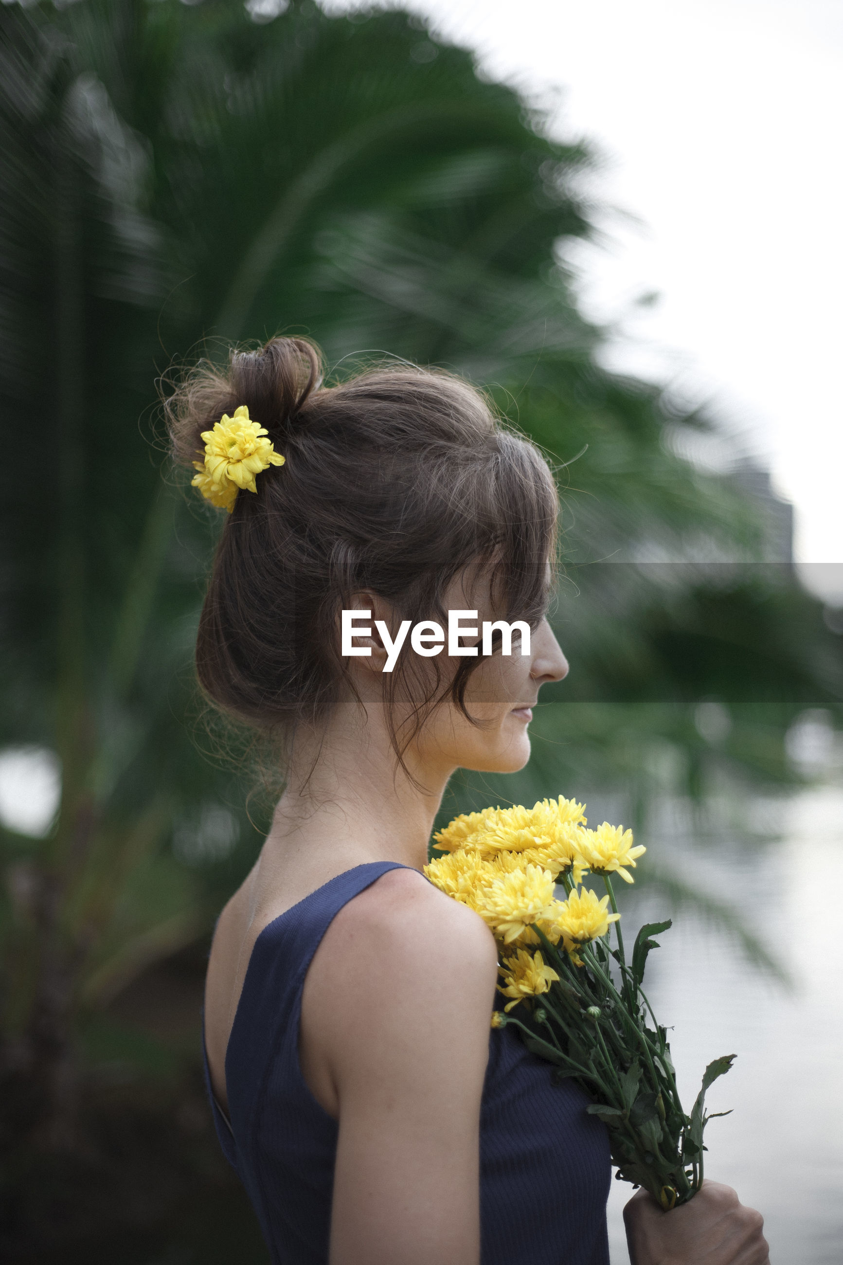 Side view of woman holding yellow flowers