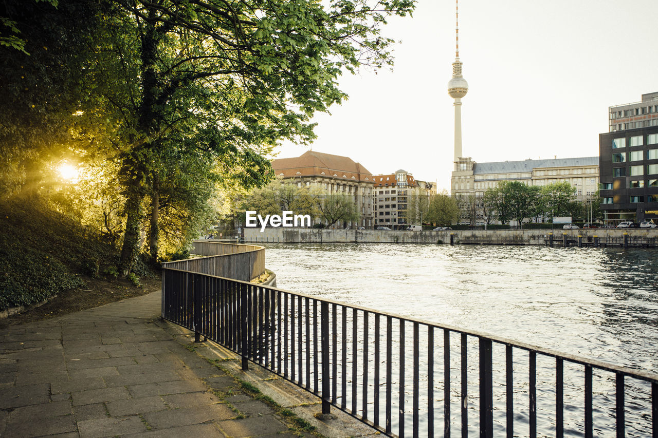Fernsehturm amidst city buildings with river in foreground
