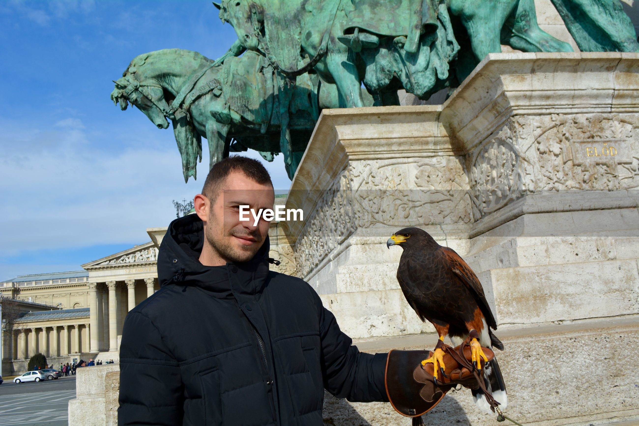 Portrait of smiling man holding bird in city