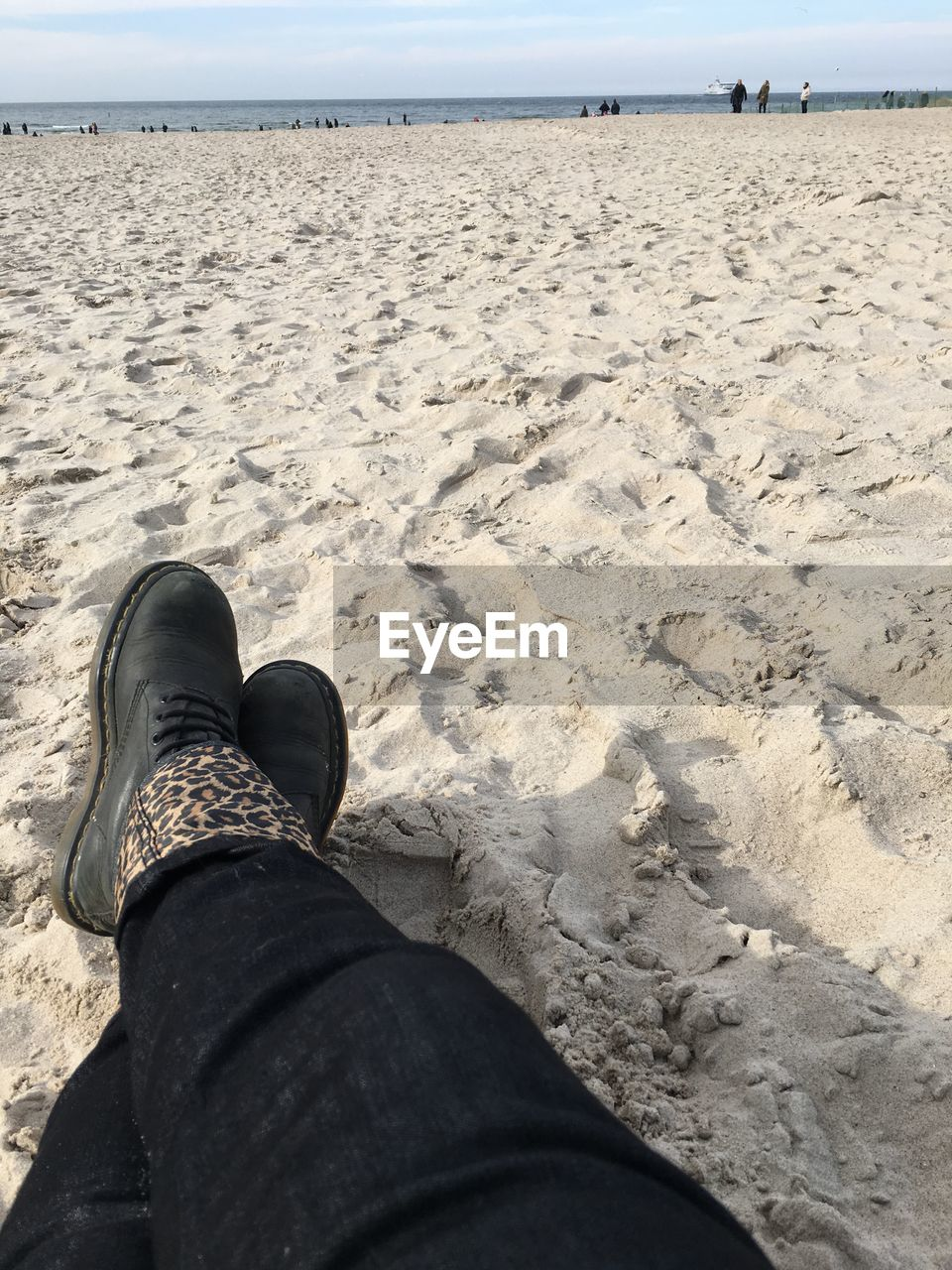 low section, human leg, land, real people, body part, personal perspective, human body part, one person, shoe, sand, beach, leisure activity, nature, lifestyles, day, sea, relaxation, unrecognizable person, sky, outdoors, jeans, human foot