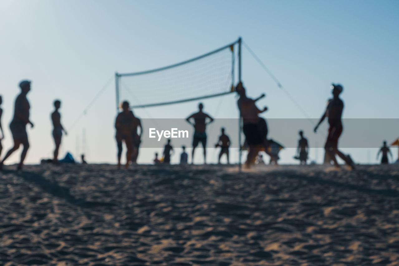 People playing ball on beach against clear sky