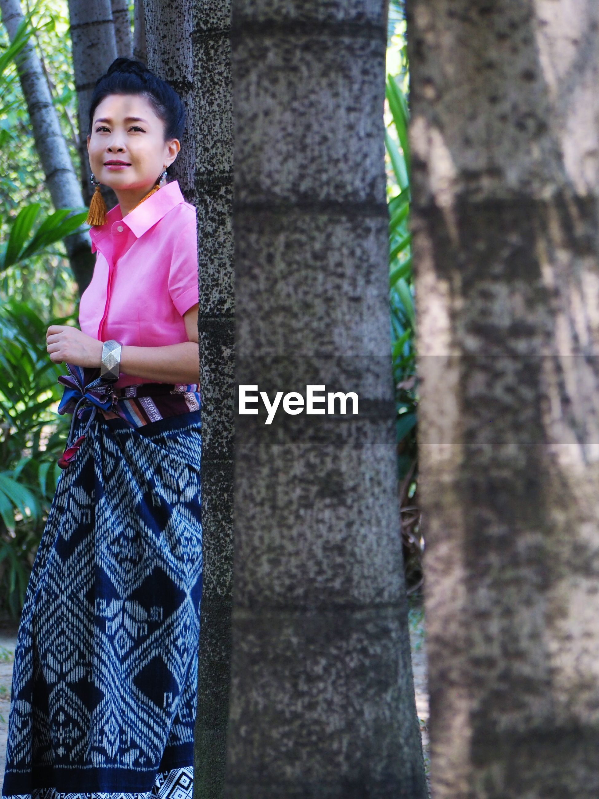 Smiling woman looking away while standing by tree in forest
