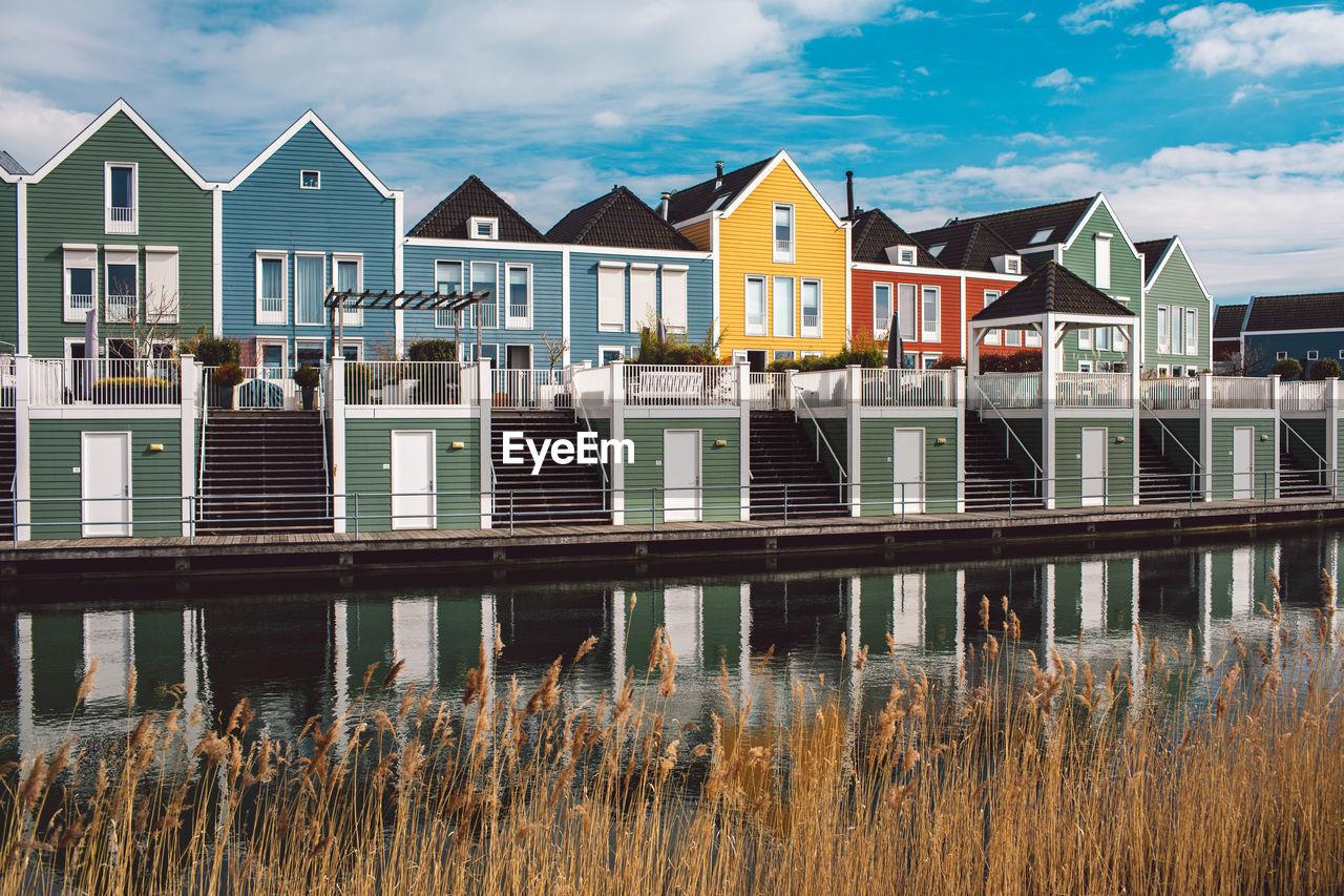 HOUSES BY LAKE AGAINST BUILDINGS