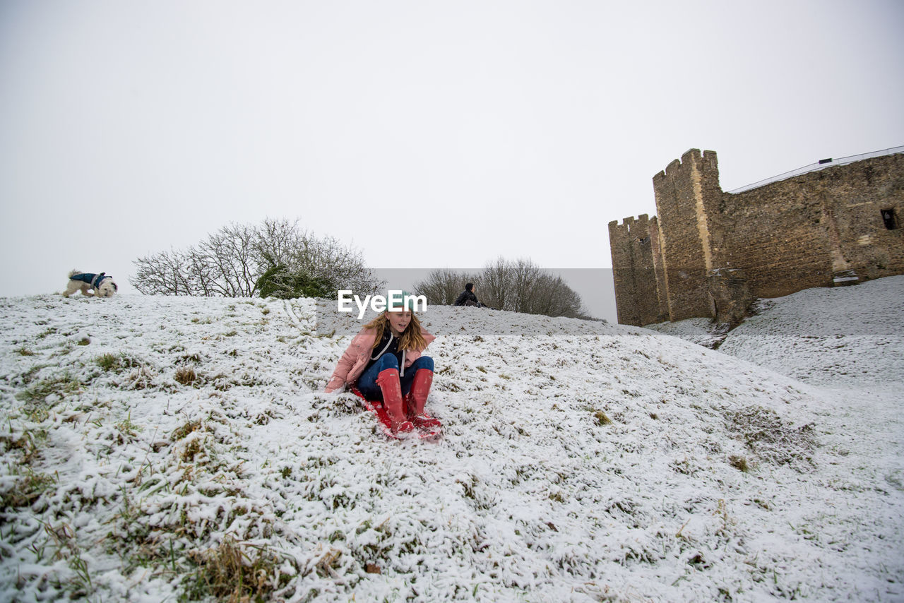 Low angle view of girl sledding on snow covered field
