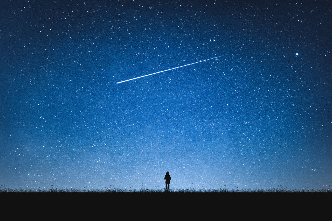 Silhouette Woman Standing Against Star Field At Night