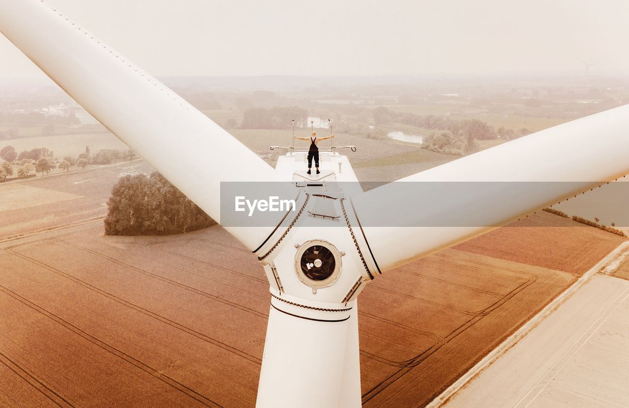 Rear View Of Man Standing On Windmill