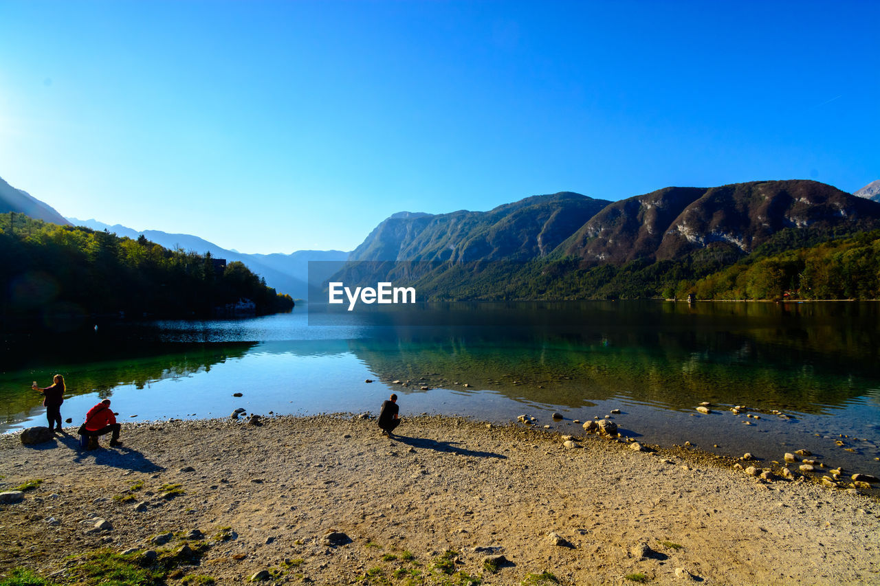 water, mountain, sky, scenics - nature, lake, beauty in nature, tranquil scene, tranquility, nature, clear sky, mountain range, day, non-urban scene, real people, blue, idyllic, reflection, copy space, men, outdoors