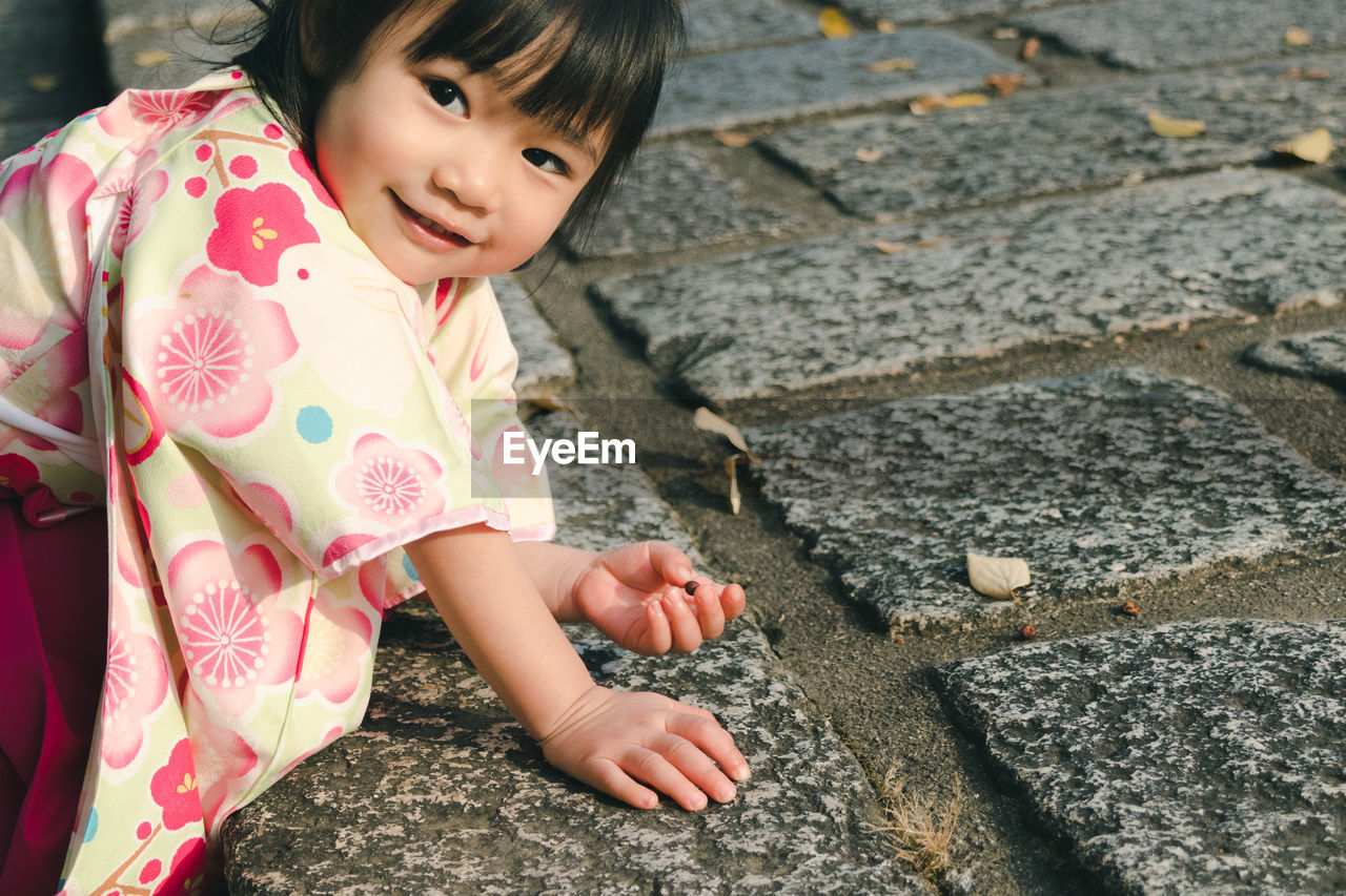 Portrait Of Cute Girl Playing On Footpath