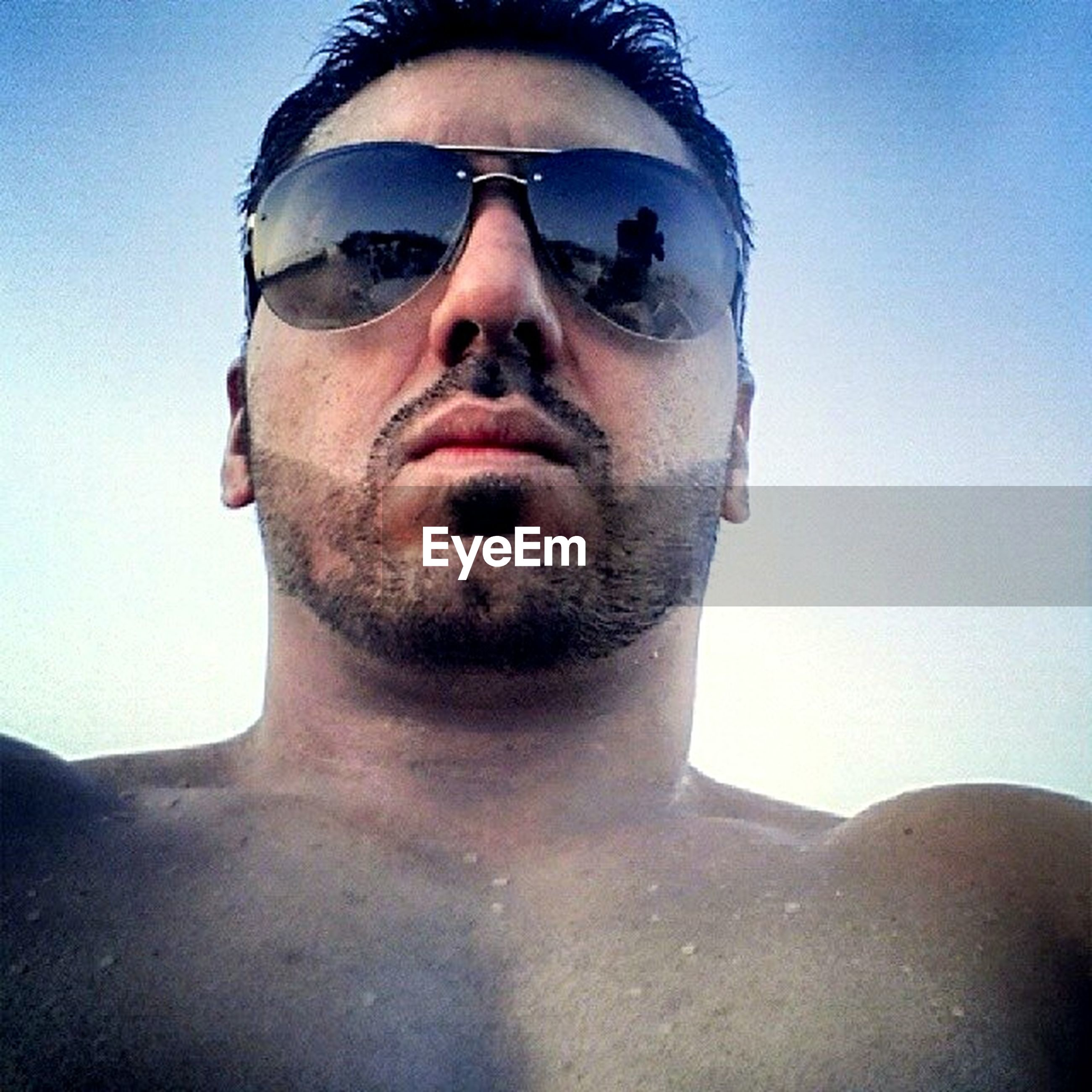 portrait, looking at camera, sunglasses, young adult, front view, person, lifestyles, young men, leisure activity, headshot, blue, beard, sunlight, mid adult men, clear sky, mid adult, smiling, eyeglasses
