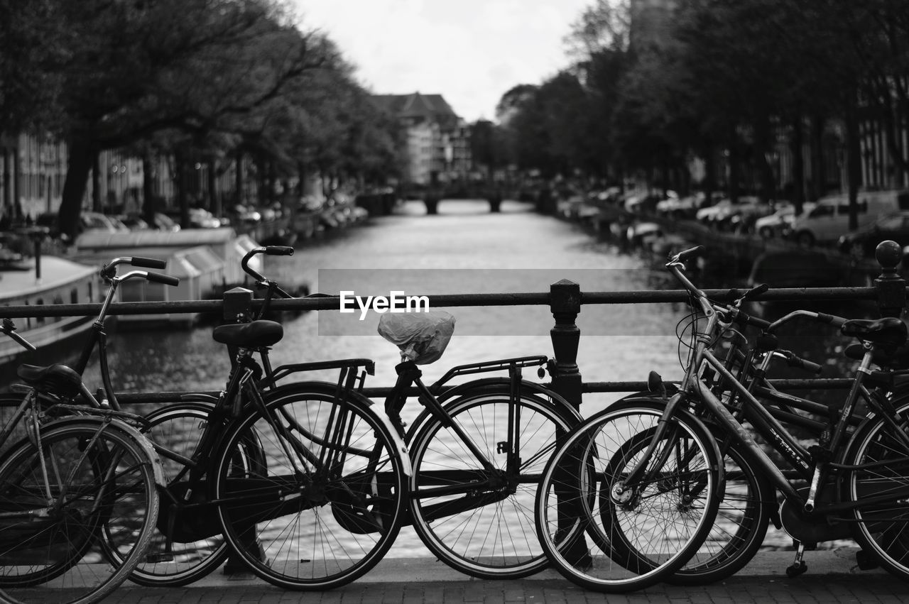 BICYCLES ON RAILING BY RIVER IN CITY
