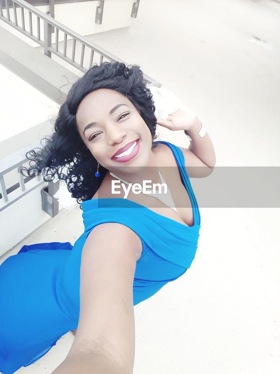 High Angle Portrait Of Smiling Mid Adult Woman In Blue Dress Standing Against Railing