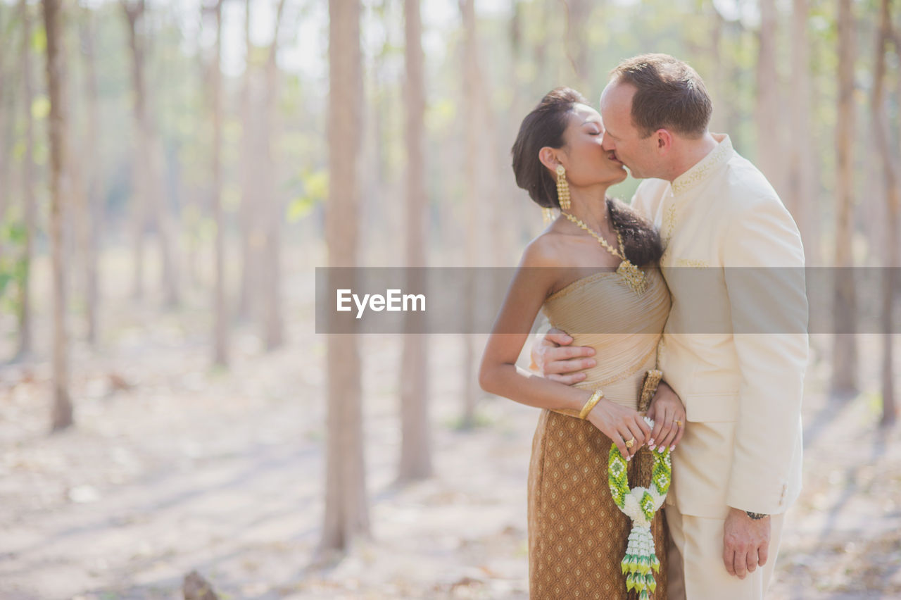 Bride and groom in traditional clothing kissing against trees