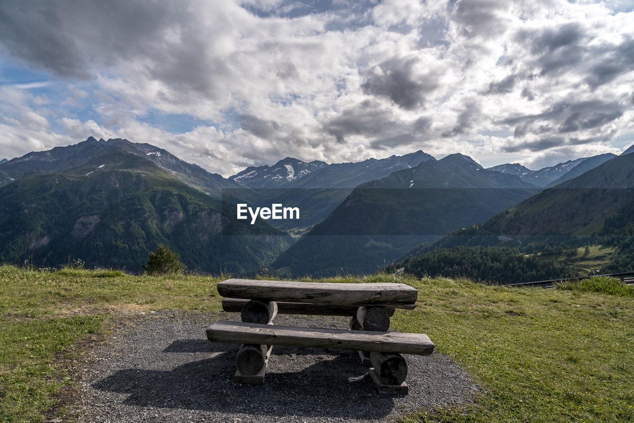Empty bench on mountain range against sky