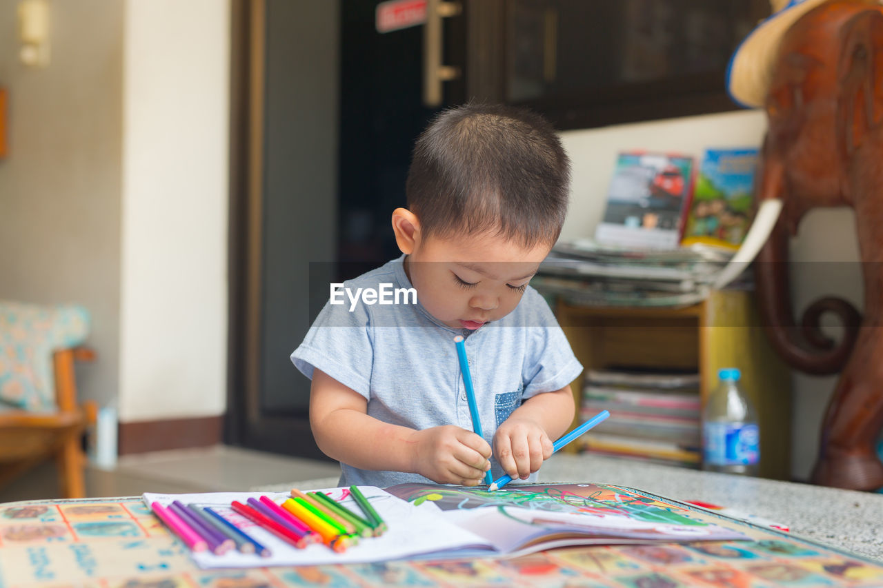 Boy Drawing On Table At Home