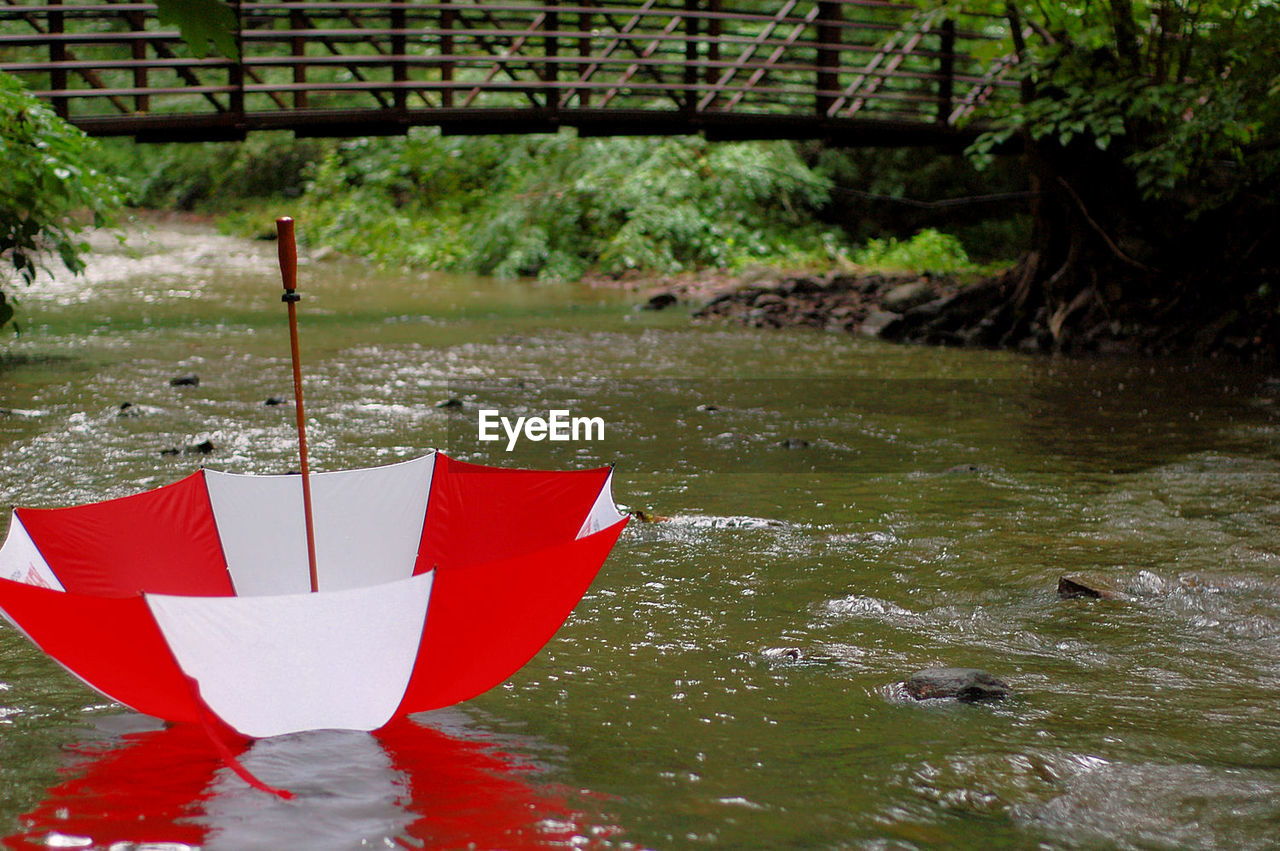 Upside down striped red and white umbrella on river