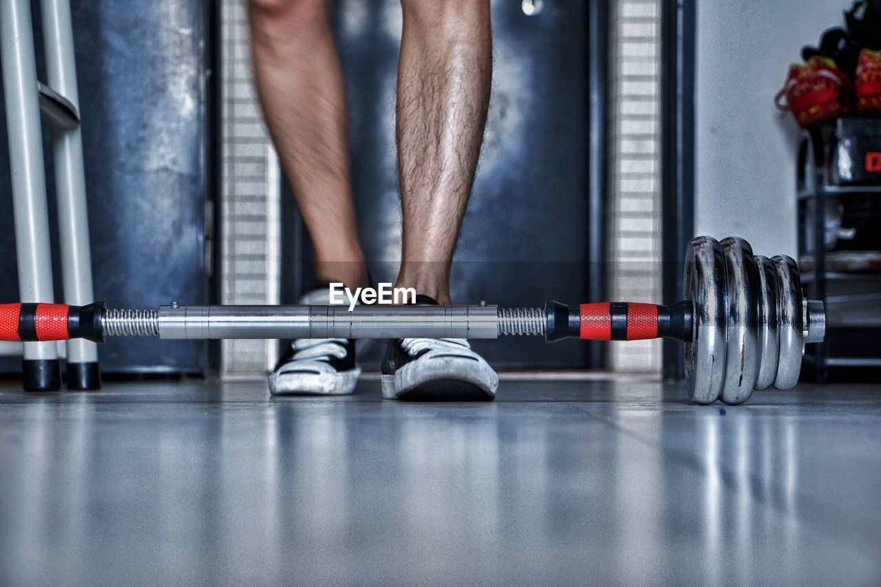 Low Section Of Man Standing By Dumbbell On Tiled Floor In Gym