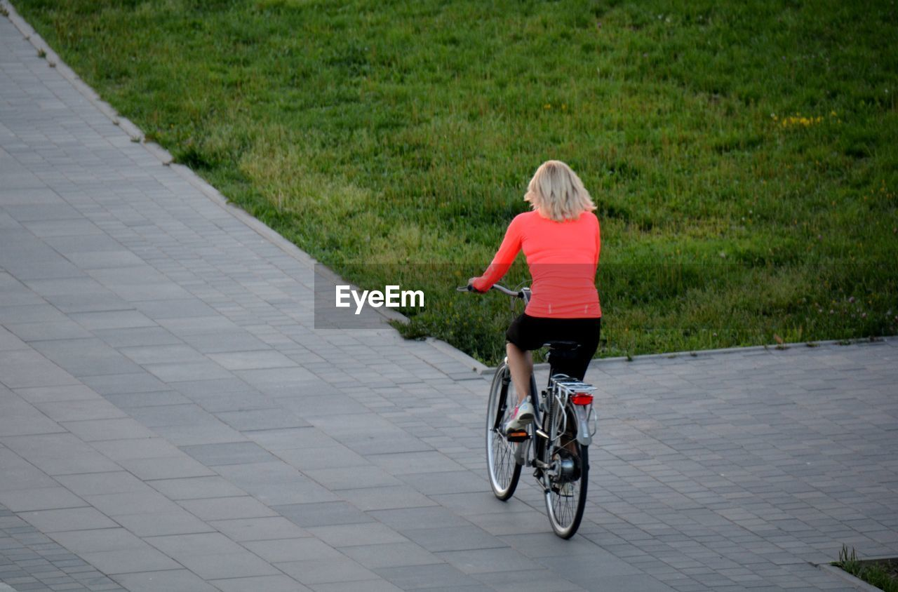 bicycle, transportation, lifestyles, one person, motion, full length, real people, rear view, sport, land vehicle, cycling, women, activity, ride, grass, leisure activity, casual clothing, riding, plant, outdoors, hairstyle