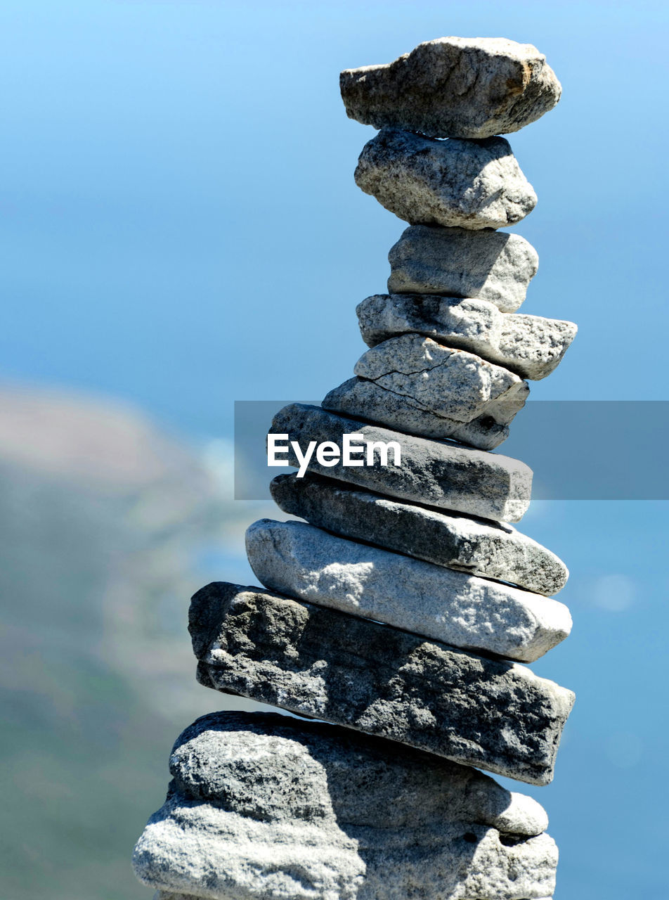 Stack Of Pebbles On Rock By Sea Against Sky