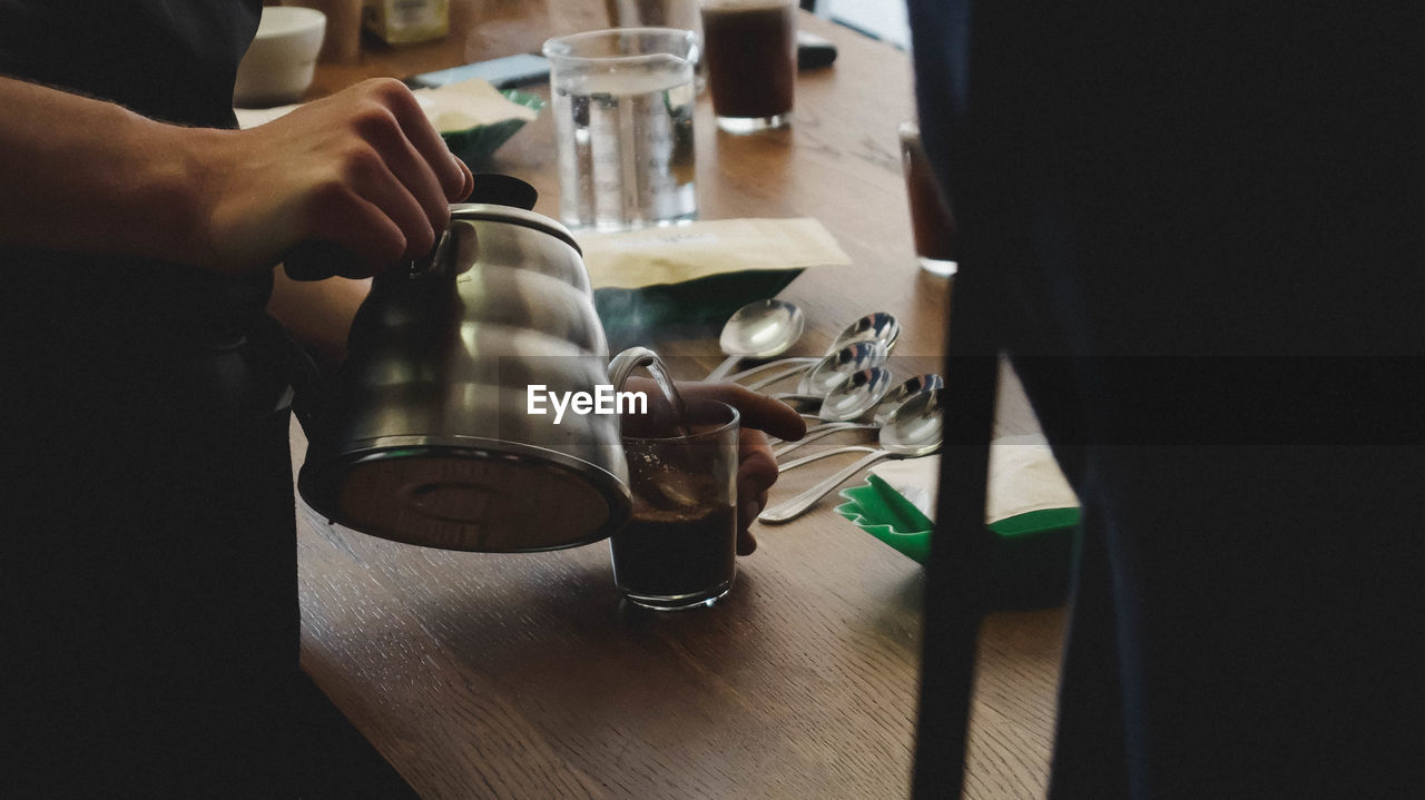 Midsection Of Man Pouring Coffee In Glass On Wooden Table