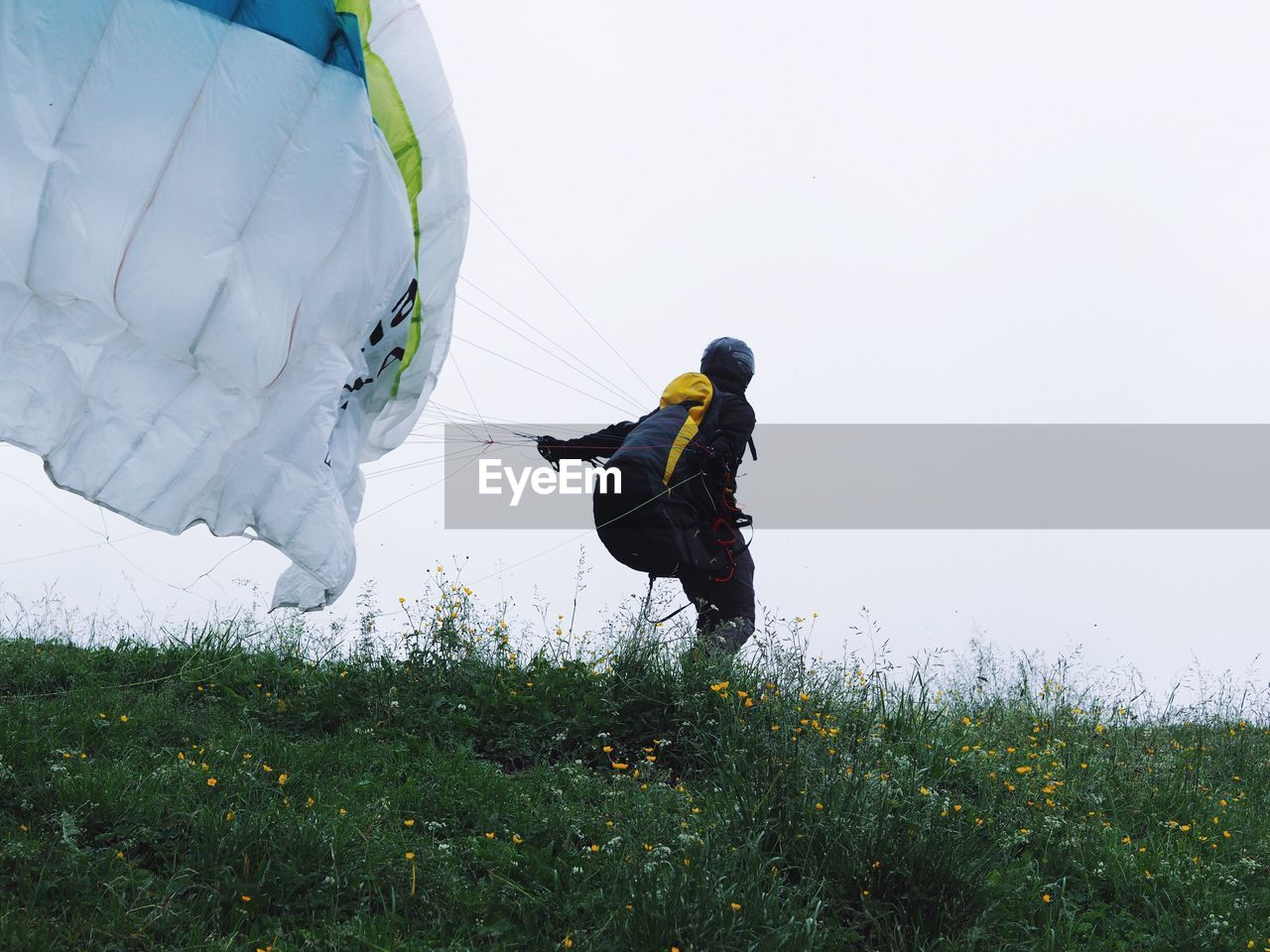 Woman Paragliding On Field Against Sky