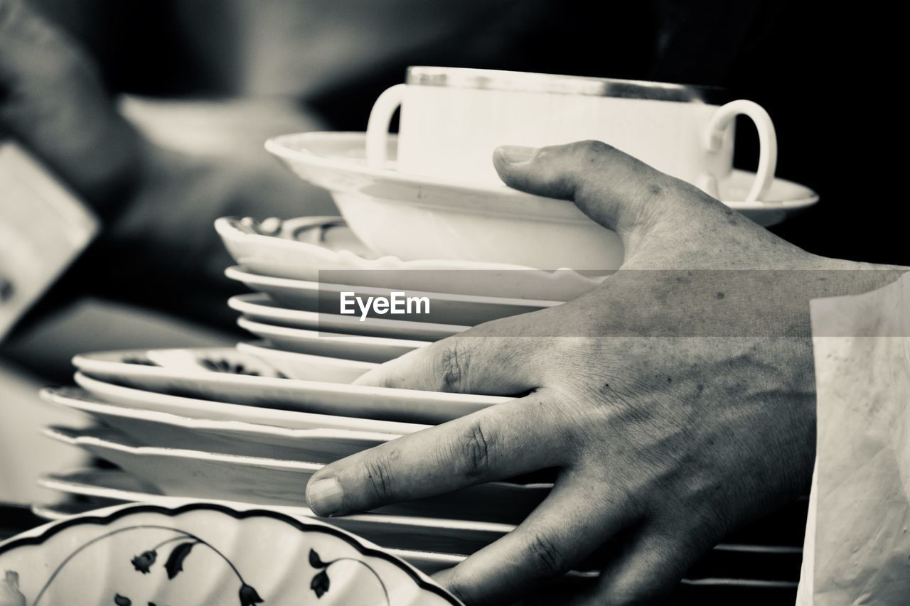 Close-up of waiter holding plates