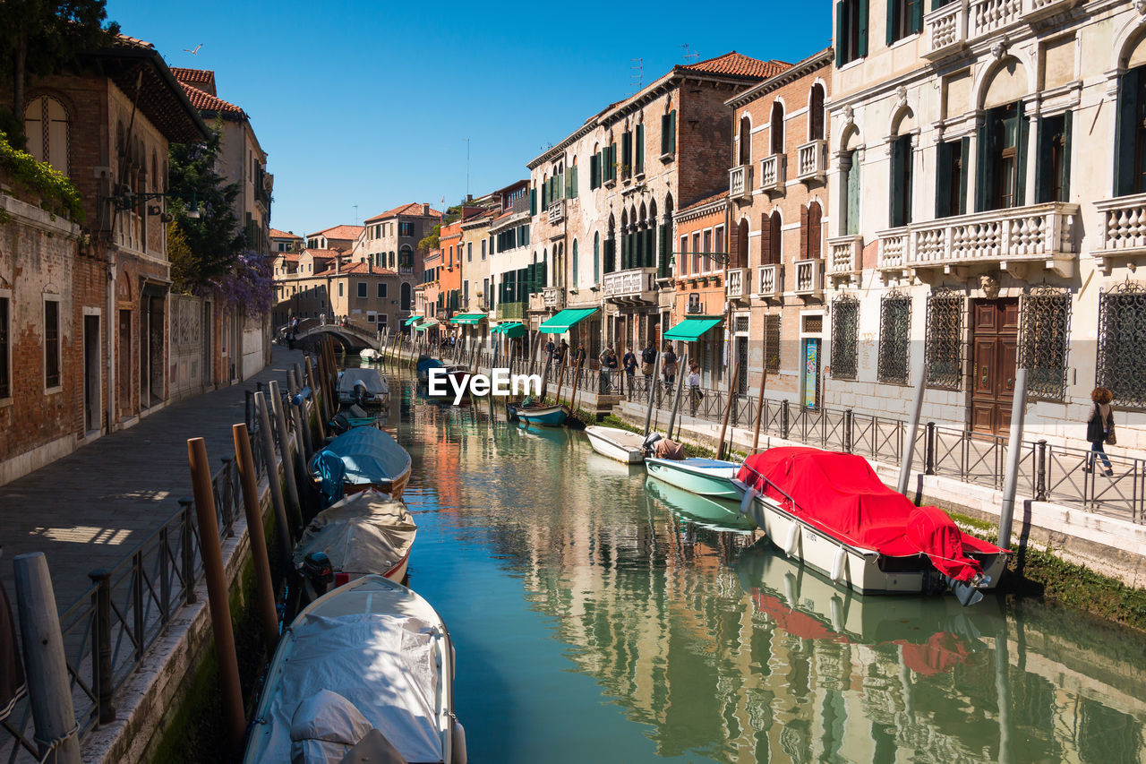 water, building exterior, built structure, nautical vessel, architecture, canal, transportation, mode of transportation, nature, city, building, reflection, sky, waterfront, day, residential district, moored, real people, incidental people, gondola - traditional boat, outdoors
