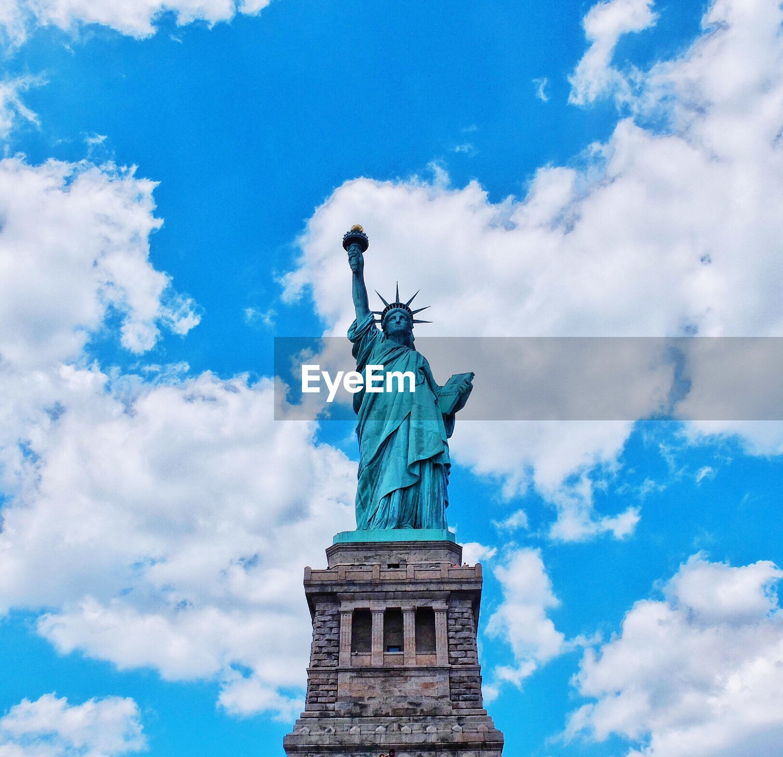 Statue of liberty against blue cloudy sky