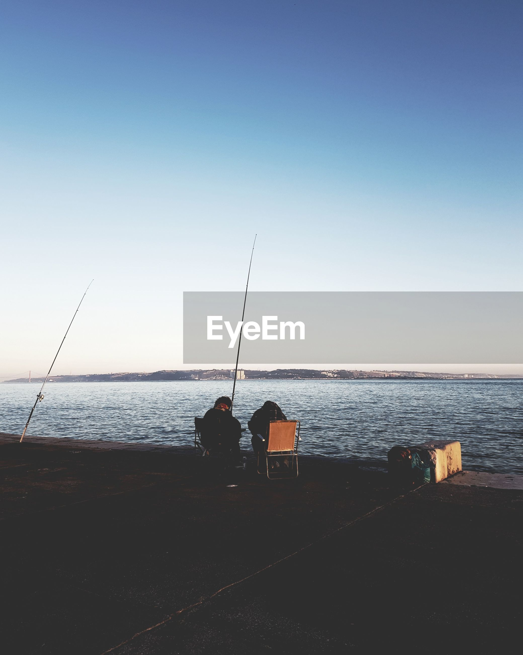 MEN FISHING ON SEA AGAINST CLEAR SKY