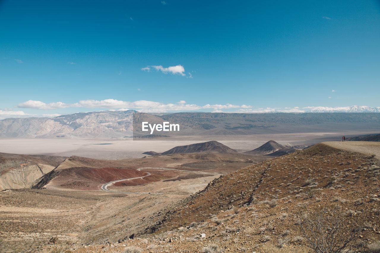 Scenic View Of Desert Landscape Against Blue Sky