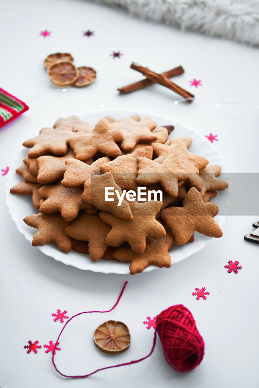 food, food and drink, cookie, still life, indoors, sweet food, table, high angle view, freshness, no people, indulgence, baked, christmas, star shape, shape, plate, close-up, celebration, gingerbread cookie, temptation