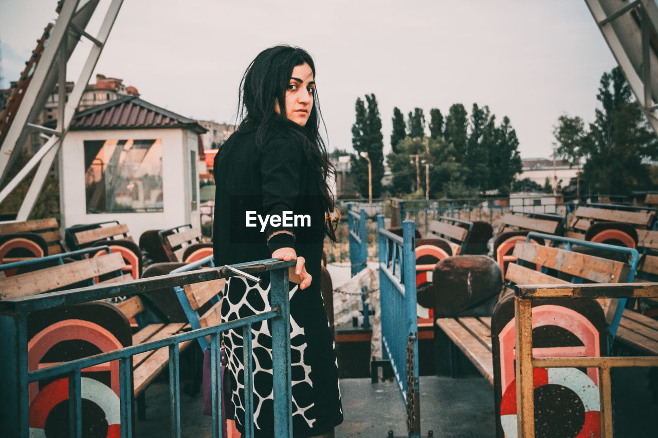 one person, real people, lifestyles, young adult, young women, focus on foreground, railing, leisure activity, transportation, clothing, architecture, standing, casual clothing, day, three quarter length, nature, women, mode of transportation, hair, hairstyle, outdoors, beautiful woman, warm clothing, contemplation