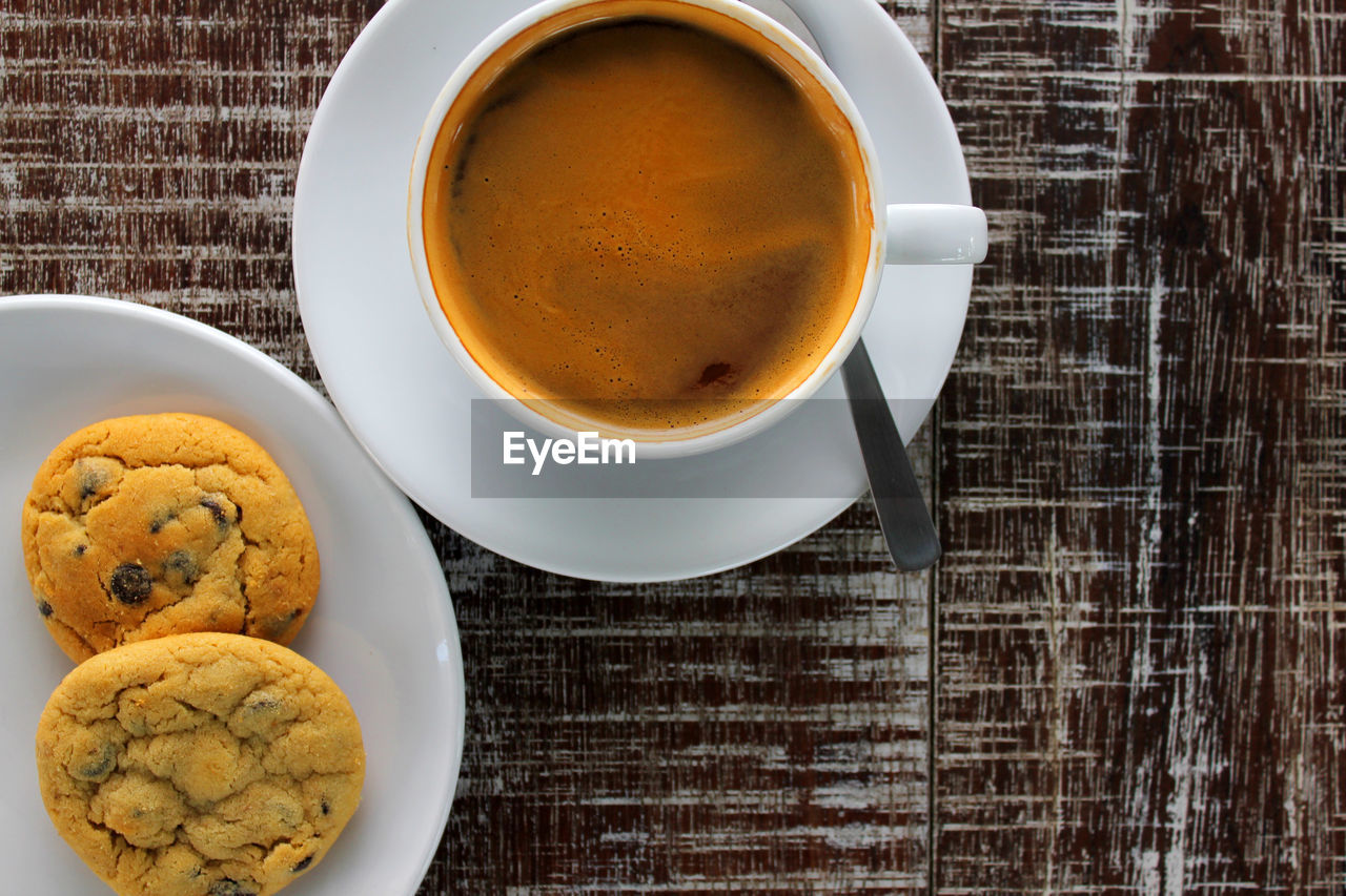 Close-Up Of Coffee Cup With Chocolate Chip Cookies On Table
